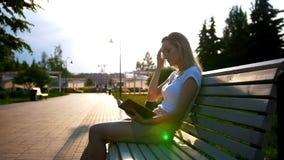 Mujer joven atractiva que lee un libro que se sienta en el banco en el parque en la puesta del sol almacen de metraje de vídeo
