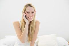 Mujer joven atractiva que llama por teléfono con su smartphone que sonríe en la cámara Foto de archivo libre de regalías