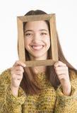 Mujer joven atractiva que lleva a cabo el marco de madera Fotografía de archivo libre de regalías