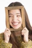 Mujer joven atractiva que lleva a cabo el marco de madera Imagen de archivo