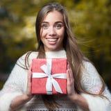 Mujer joven atractiva que lleva a cabo rojo presente Fotografía de archivo