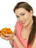 Mujer joven atractiva que lleva a cabo un puñado de anillo condimentado cebolla Foto de archivo libre de regalías