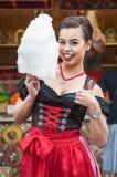 Mujer joven atractiva que lleva un vestido tradicional del Dirndl con seda del caramelo de algodón en el Oktoberfest Imagen de archivo libre de regalías