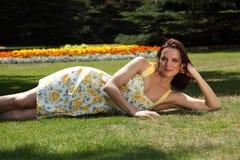 Mujer joven atractiva que miente en hierba en sol del verano Foto de archivo