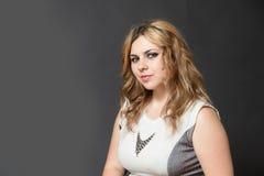 Mujer joven atractiva que mira de lado la cámara Imágenes de archivo libres de regalías