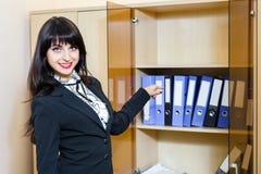 Mujer joven atractiva que muestra a las carpetas con los documentos en offi Imagen de archivo