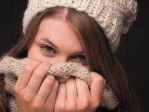Mujer joven atractiva que oculta su cara con una bufanda Fotos de archivo