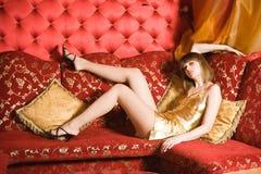 Mujer joven atractiva que pone en el sofá rojo fotos de archivo libres de regalías