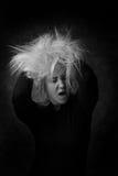 Mujer joven atractiva que pone las manos en su pelo despeinado Imágenes de archivo libres de regalías