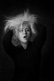 Mujer joven atractiva que pone las manos en su pelo despeinado Imagenes de archivo