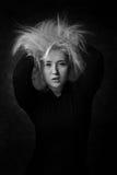 Mujer joven atractiva que pone las manos en su pelo despeinado Fotos de archivo libres de regalías