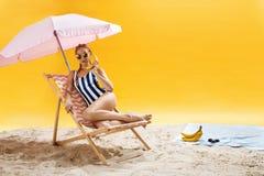 Mujer joven atractiva que presenta en la silla de playa rosada que se ríe Foto de archivo