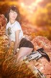 Mujer joven atractiva que presenta en rocas herbosas fotografía de archivo libre de regalías