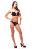 Mujer joven atractiva que presenta en un bikini negro aislado en el fondo blanco Fotografía de archivo libre de regalías