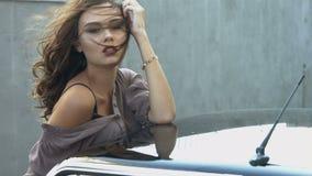 Mujer joven atractiva que presenta para una revista de moda en el coche almacen de video