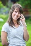 Mujer joven atractiva que ríe entonces invitando al teléfono Fotografía de archivo libre de regalías