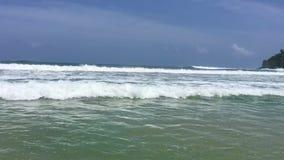 Mujer joven atractiva que salta y que juega en las ondas en el océano