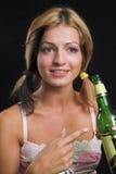 Mujer joven atractiva que señala en una botella de cerveza Fotografía de archivo libre de regalías