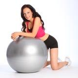 Mujer joven atractiva que se arrodilla con la bola de la aptitud Imagen de archivo libre de regalías