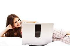 Mujer joven atractiva que se relaja en cama con la computadora portátil Fotografía de archivo