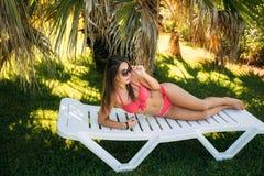 Mujer joven atractiva que se relaja en silla de cubierta Mujer hermosa en el bikini rosado que miente cerca del mar foto de archivo libre de regalías