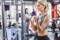 Mujer joven atractiva que se resuelve con pesas de gimnasia imagenes de archivo