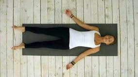Mujer joven atractiva que se resuelve en casa, haciendo ejercicio de la yoga, mintiendo en la actitud del cadáver o del cadáver d almacen de metraje de vídeo
