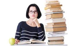 Mujer joven atractiva que se sienta al lado de la pila de libro con un app Imágenes de archivo libres de regalías