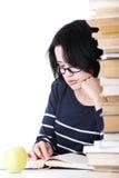 Mujer joven atractiva que se sienta al lado de la pila de libro con un app Foto de archivo