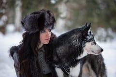 Mujer joven atractiva que se sienta con el perro fornido que mira a un lado imagenes de archivo