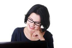 Mujer joven atractiva que se sienta delante de un ordenador portátil. Fotos de archivo