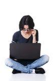 Mujer joven atractiva que se sienta delante de un ordenador portátil. Fotos de archivo libres de regalías