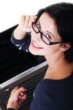 Mujer joven atractiva que se sienta delante de un ordenador portátil. Imagen de archivo