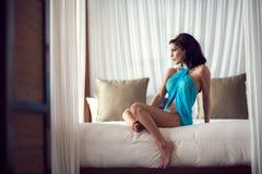 Mujer joven atractiva que se sienta en cama Fotografía de archivo libre de regalías