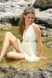 Mujer joven atractiva que se sienta en el agua Imagenes de archivo