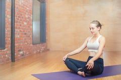 Mujer joven atractiva que se sienta en la posición de loto en un studi de la yoga Foto de archivo