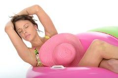 Mujer joven atractiva que se sienta en los anillos de goma que llevan un traje de baño imagenes de archivo