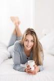 Mujer joven atractiva que se sienta en su cama Fotos de archivo libres de regalías