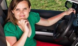 Mujer joven atractiva que se sienta en su coche foto de archivo
