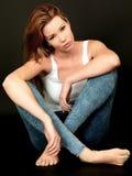 Mujer joven atractiva que se sienta en suelo Fotografía de archivo libre de regalías