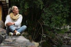 Mujer joven atractiva que se sienta en un bosque frío que disfruta de la visión Fotos de archivo