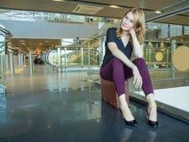 Mujer joven atractiva que se sienta en una maleta en el lobb del aeropuerto Imagen de archivo
