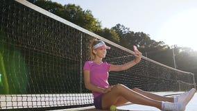 Mujer joven atractiva que se sienta en una pista de tenis cerca de red mientras que toma el selfie en el teléfono elegante metrajes