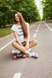 Mujer joven atractiva que se sienta a piernas cruzadas en un longboard en el camino en el parque skateboarding outdoors Fotografía de archivo
