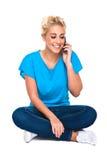 Mujer joven atractiva que sonríe en el teléfono celular Fotos de archivo libres de regalías