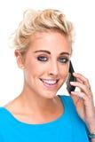 Mujer joven atractiva que sonríe mientras que en el teléfono celular Imagen de archivo