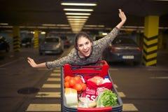 Mujer joven atractiva que sonríe y que empuja un carro de la compra en el estacionamiento del supermercado Concepto de venta, des Foto de archivo