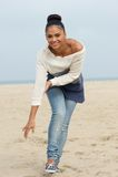 Mujer joven atractiva que sonríe y que camina en la playa Fotografía de archivo