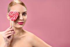Mujer joven atractiva que sostiene el caramelo fotos de archivo libres de regalías