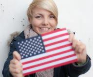 Mujer joven atractiva que sostiene la bandera de los E.E.U.U. Imagenes de archivo